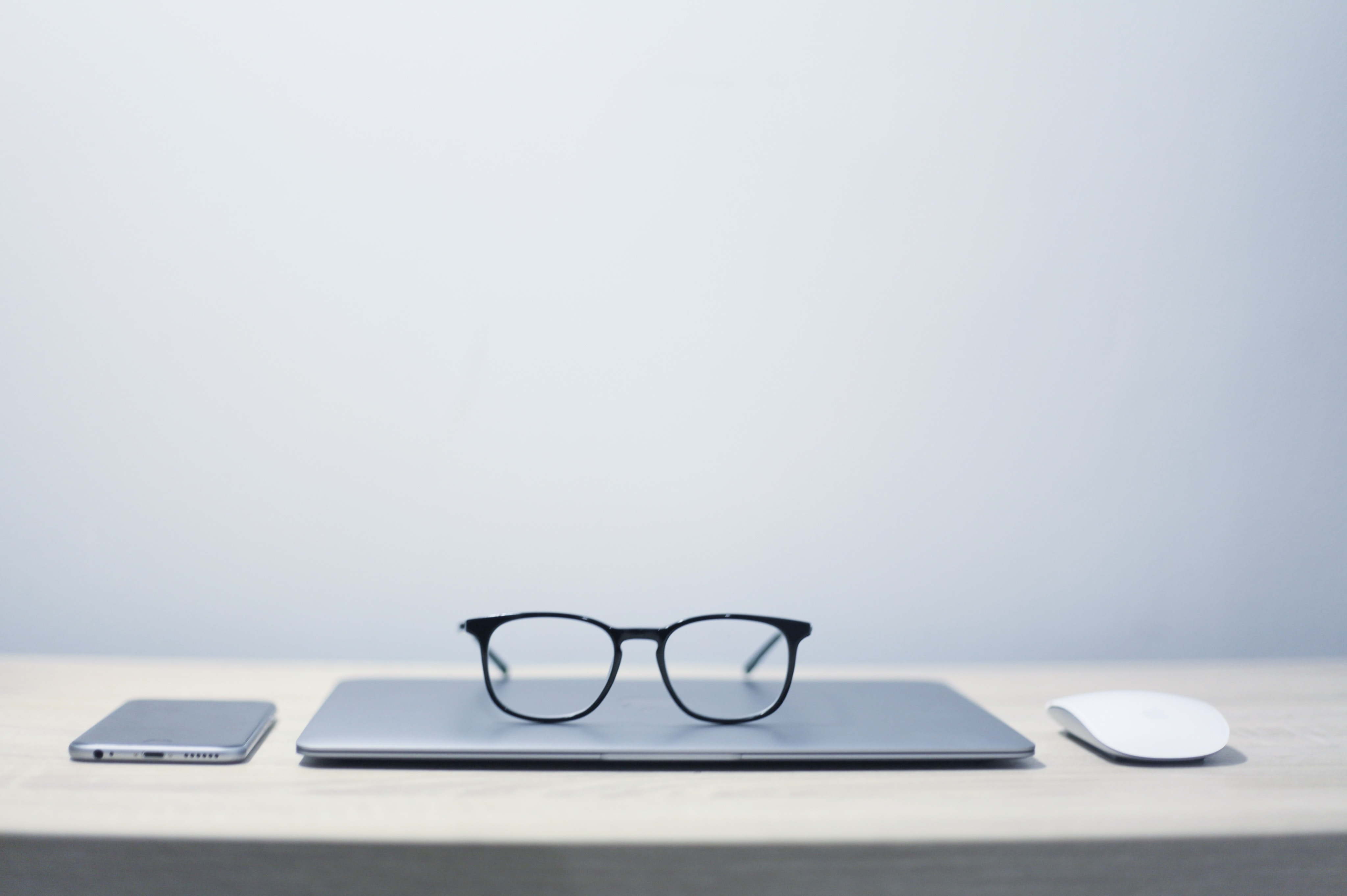 closed laptop on a desk with glasses