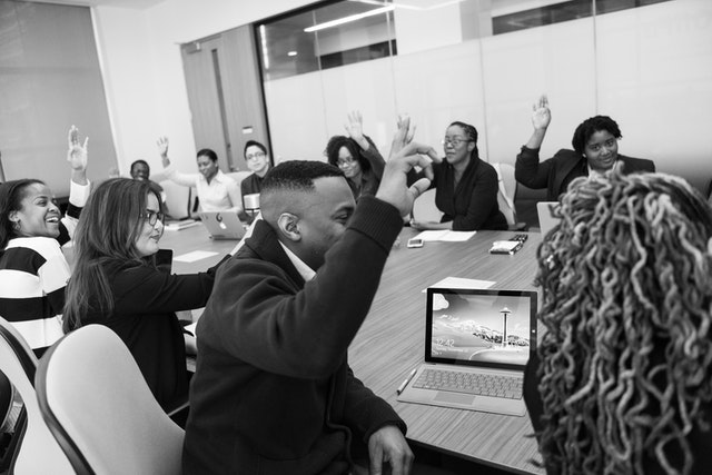 classroom of adult students with computers raising hands for help