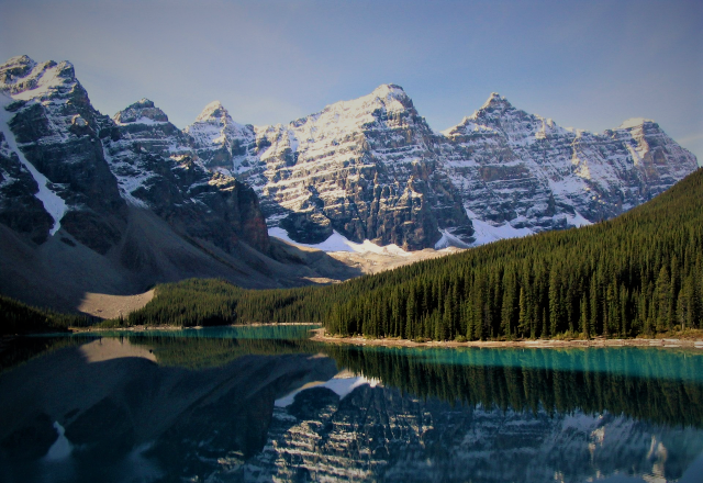 A bright blue lake with evergreen trees and snow covered mountains in the background