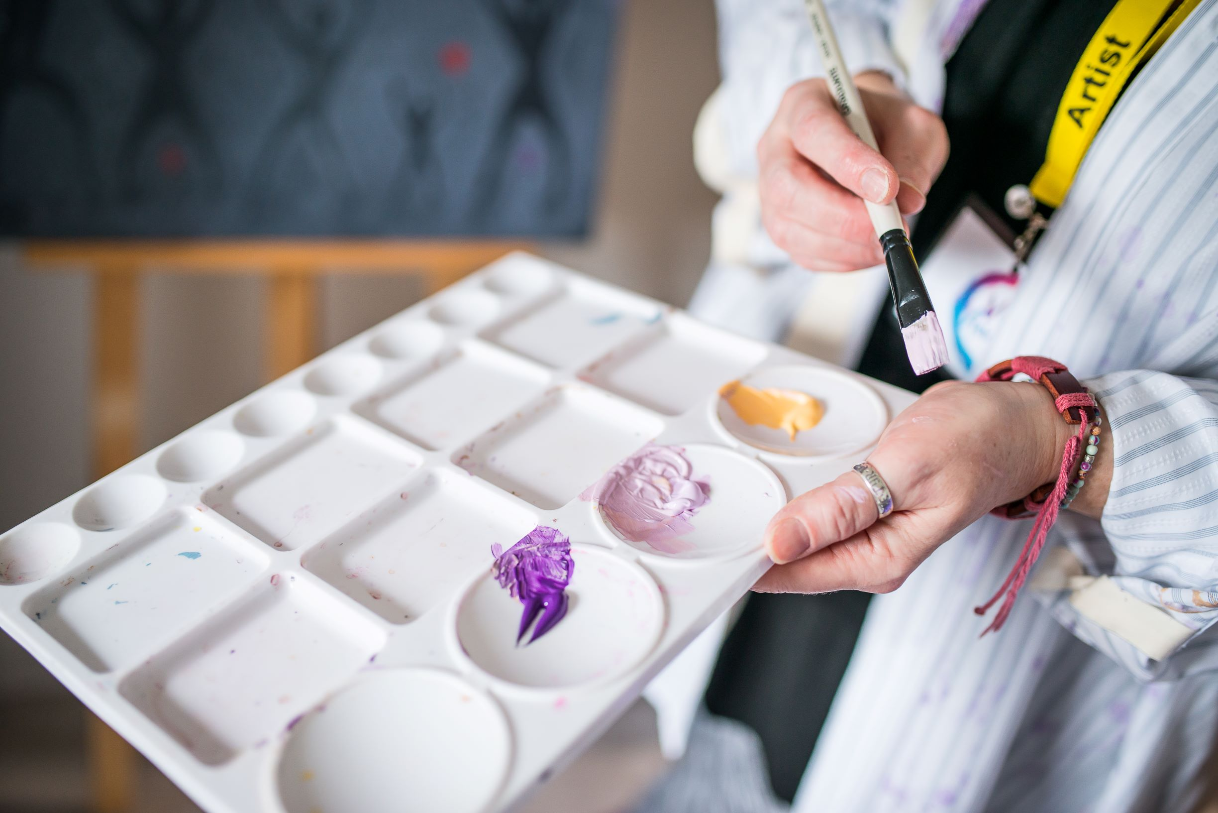 picture of a woman holding a paint pallette and brush