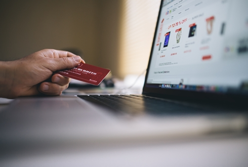 woman holding credit card and shopping online