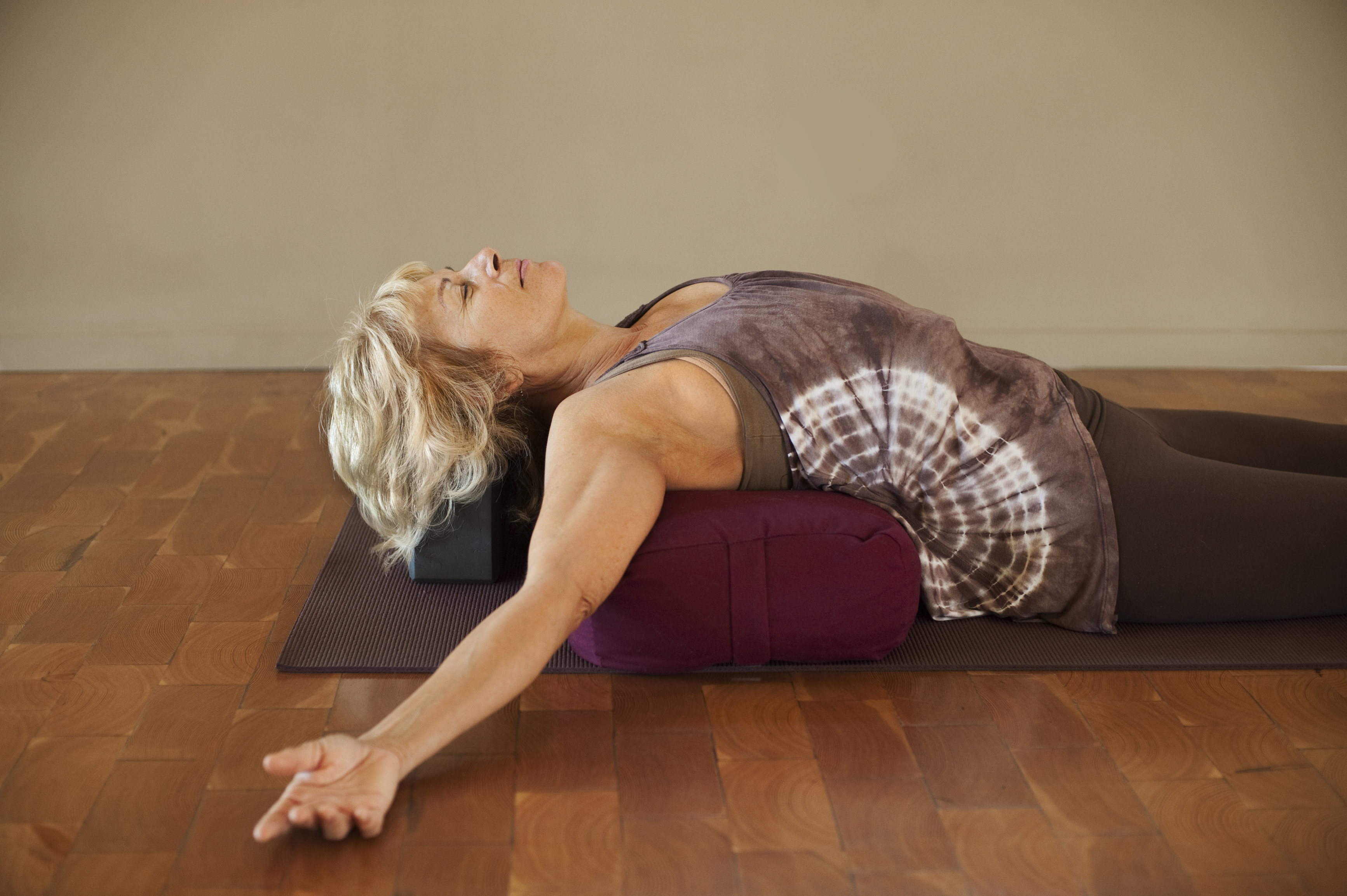 Woman reclining over a bolster yoga pose