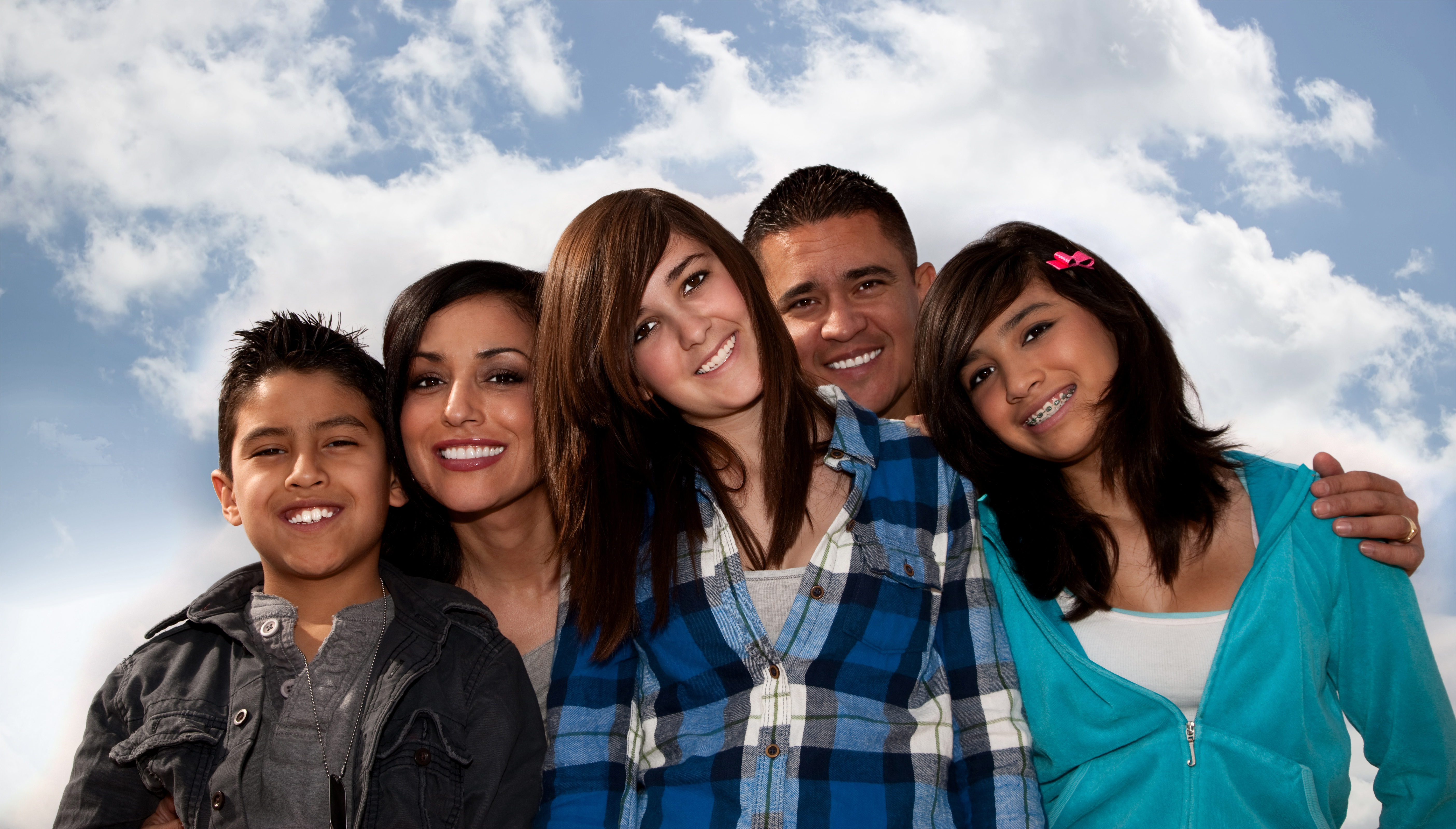 Hispanic family of two teenage girls and one young boy with mom and dad