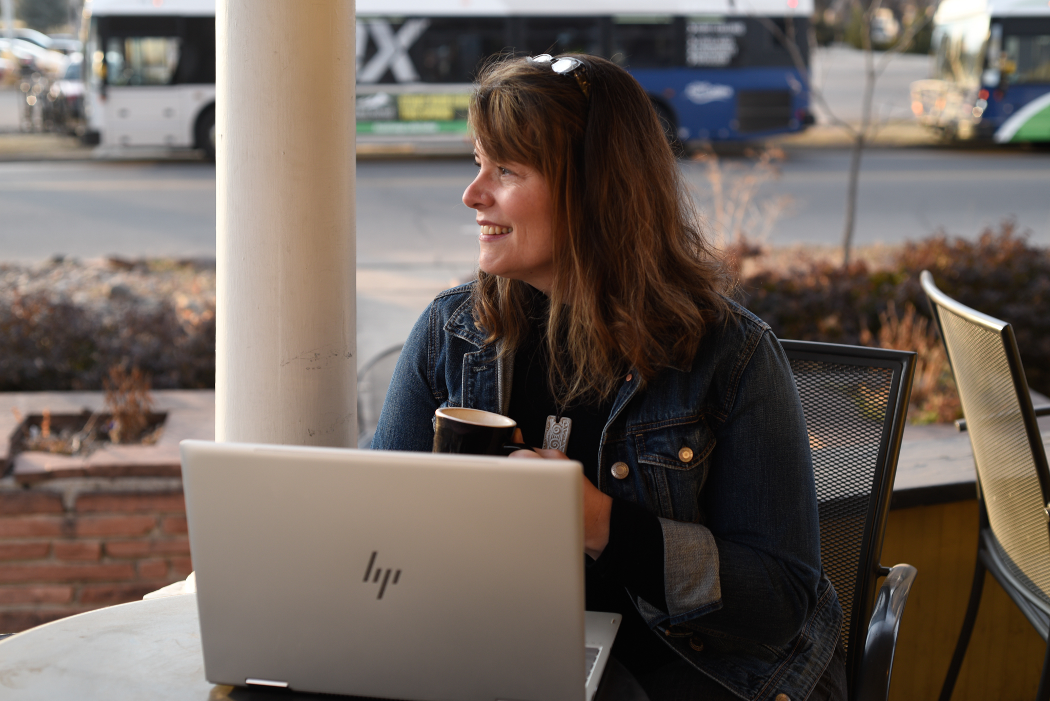 Crushing it on LinkedIn biography image of woman at table with laptop