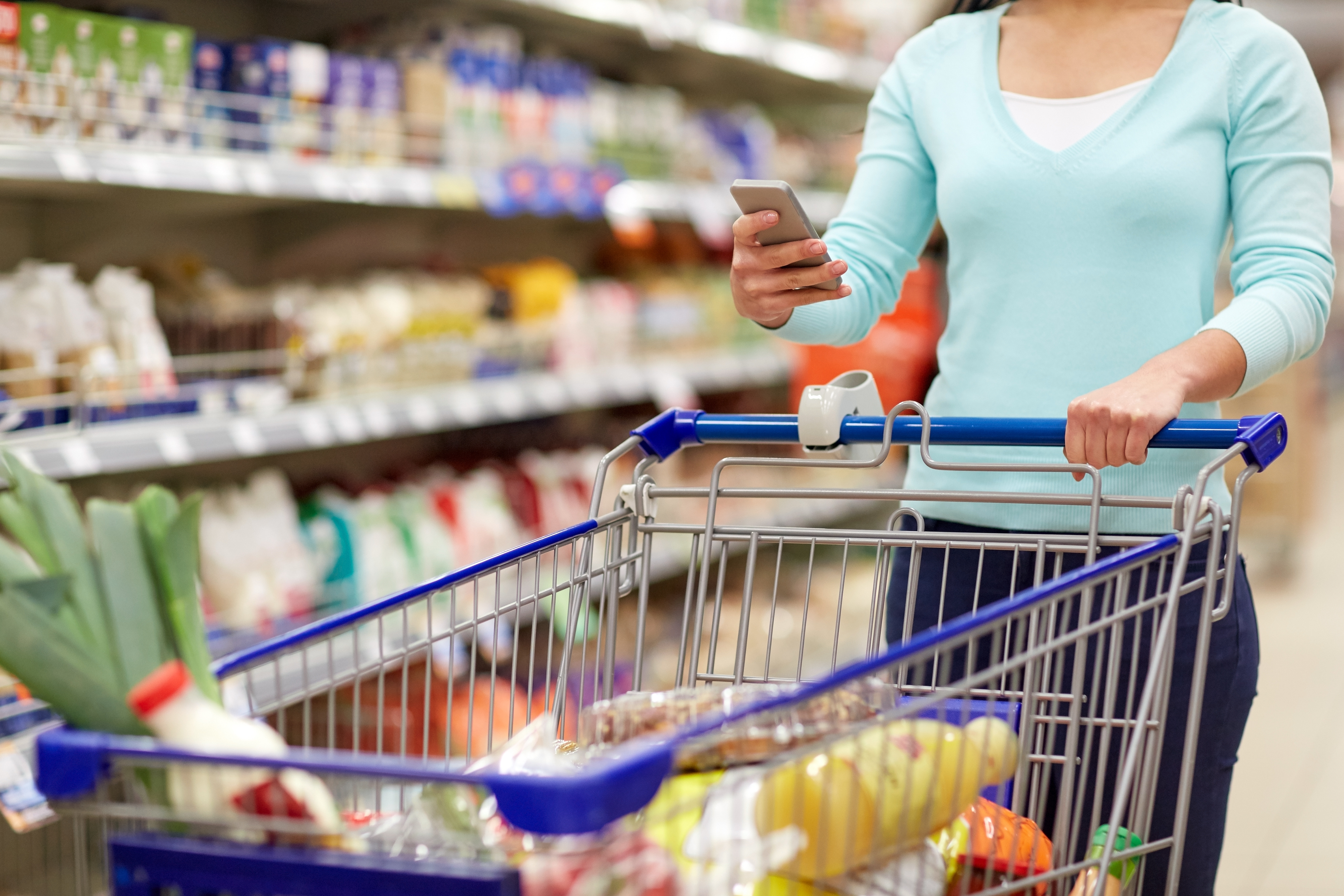 women in grocery store with cart and looking at phone