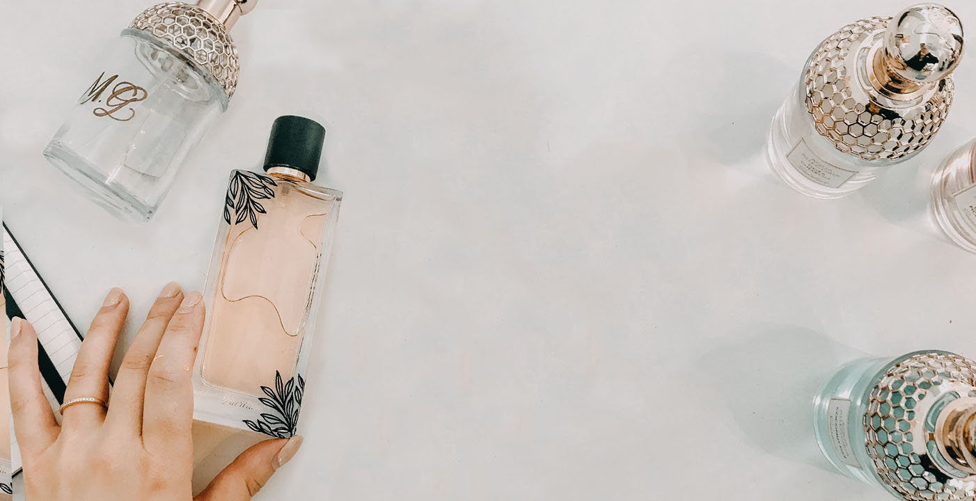 On-Site Event Calligraphy Artist holding Luxury brand bottles customized with floral illustrations and hand-lettering