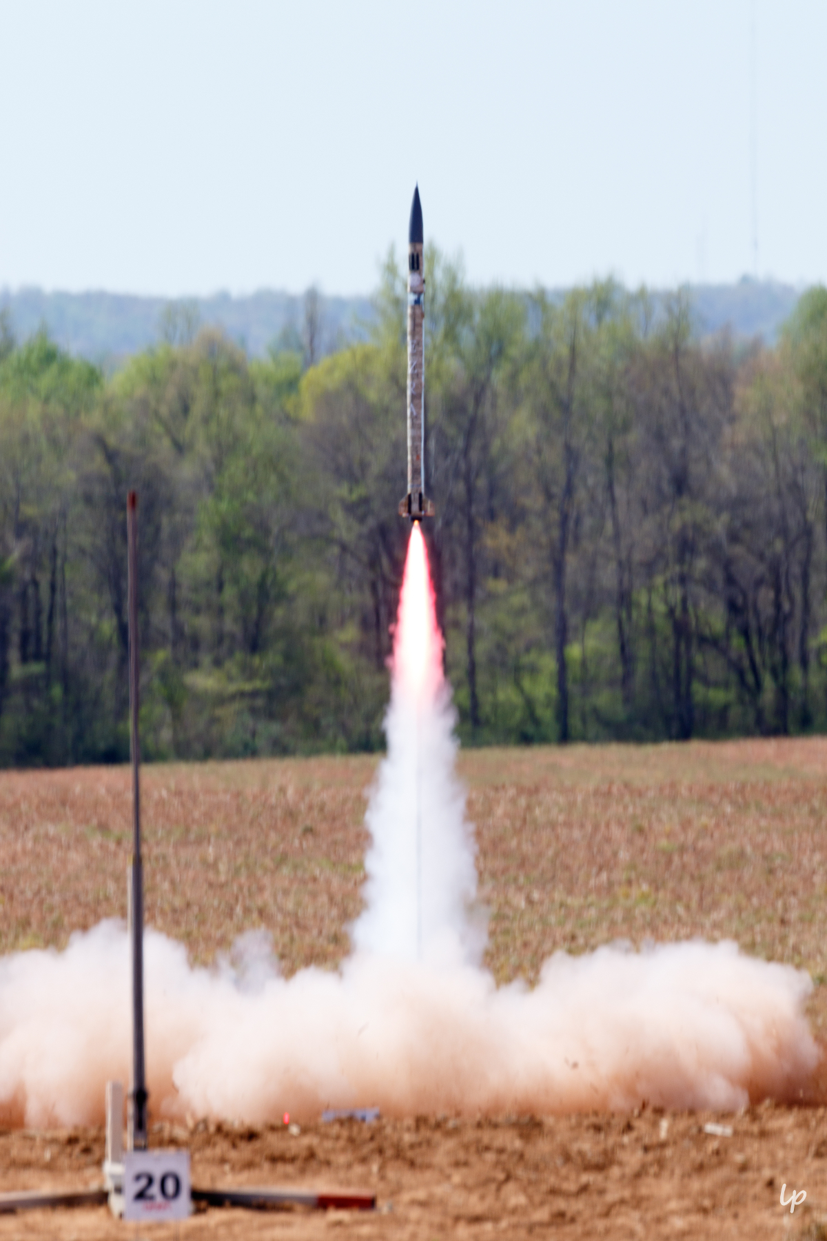 Photo of Cornell Rocketry Team's rocket, Ezra, leaving the launch pad