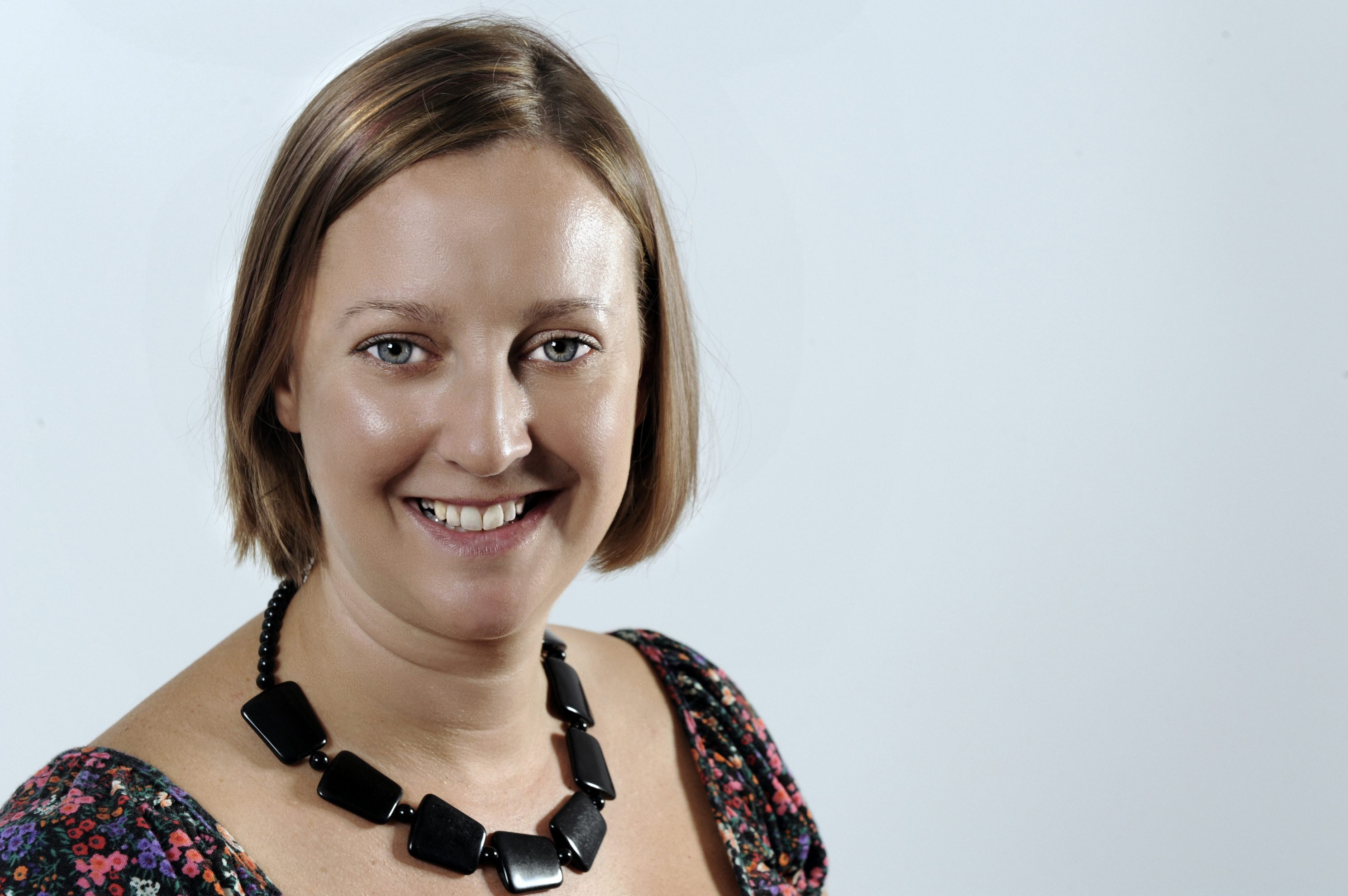 Photo of a white woman with a mousy brown straight bob. It is a professional head shot with her smiling at the camera, wearing a chunky black necklace and flowery t-shirt. The background is a light grey/blue blank studio.