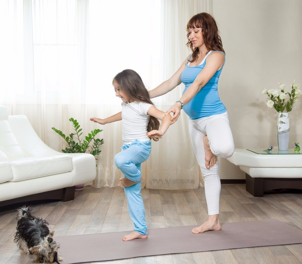 mom and daughter doing yoga with dog