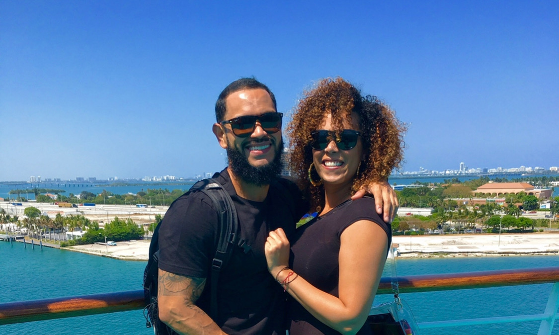 Hispanic couple on vacation in a cruise ship in the ocean with beard and curly hair
