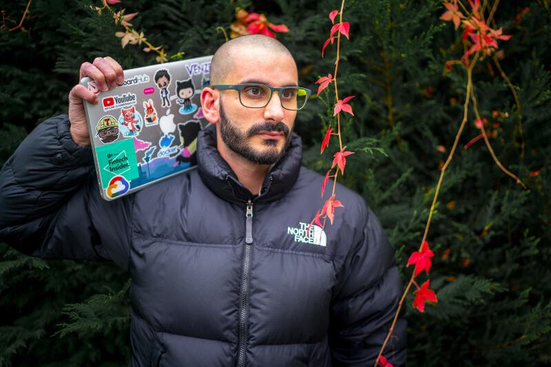 bald bearded man holding laptop on shoulder