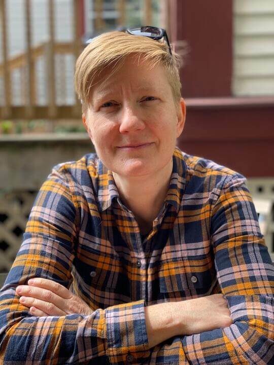 woman with short hair sitting with arms crossed wearing a plaid shirt