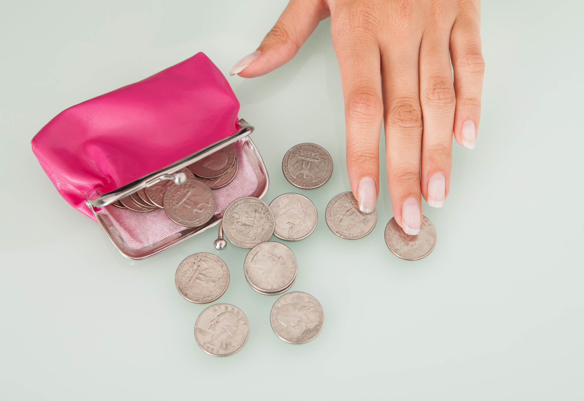 female hand counting coins from an open pink purse to signify how to become fabulously frugal course