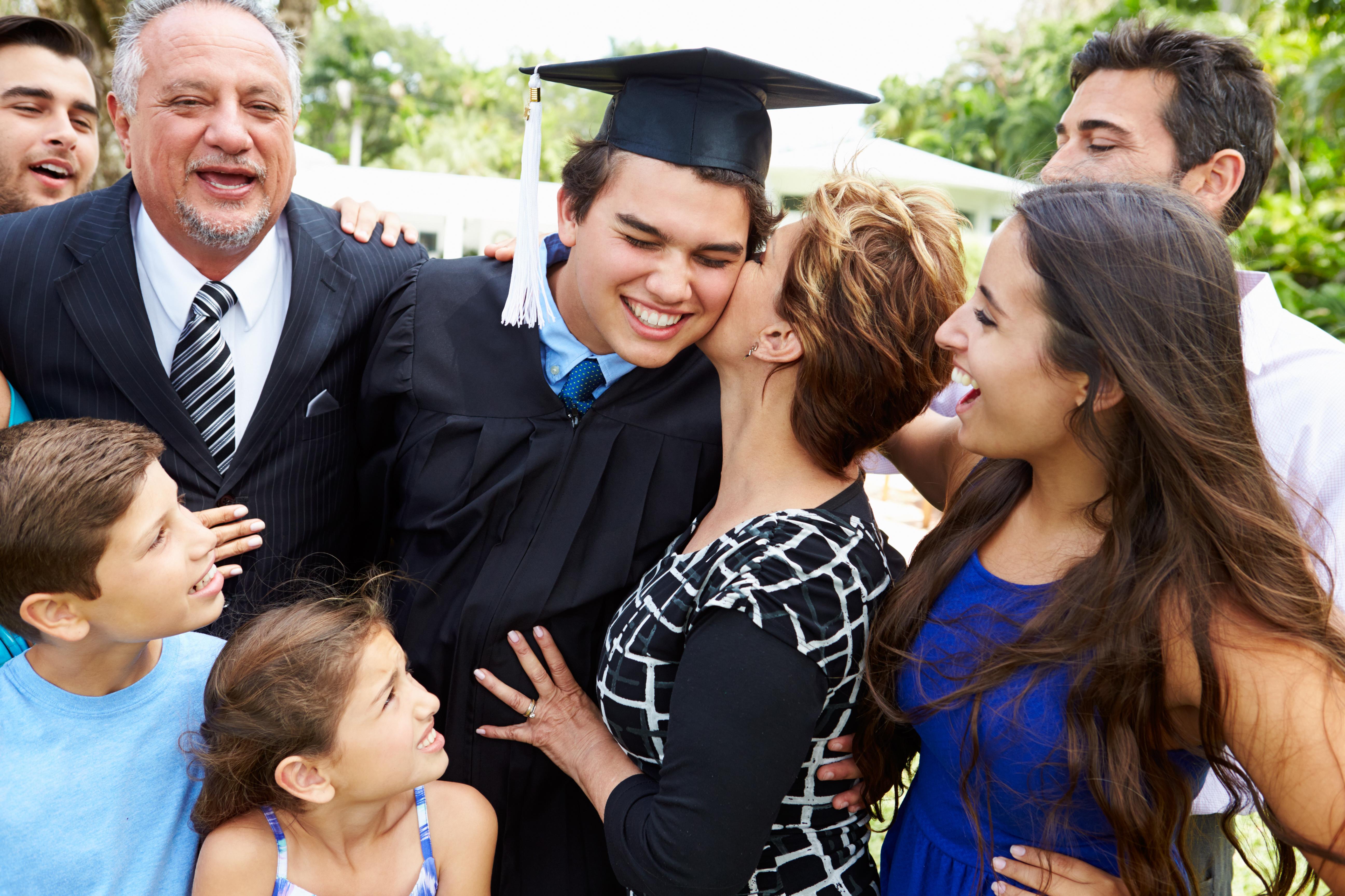 Hispanic family celebrating graduation with teenage high school graduate