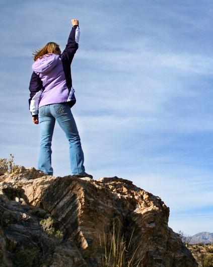 Kvinna på toppen av ett berg med segergest
