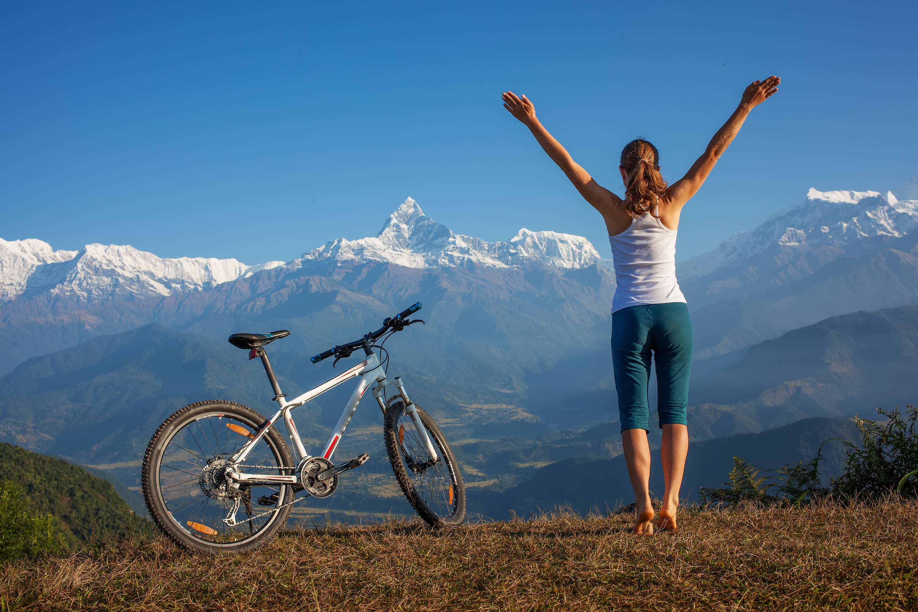 Healthy Women standing next to her mountain bike overlooking a view
