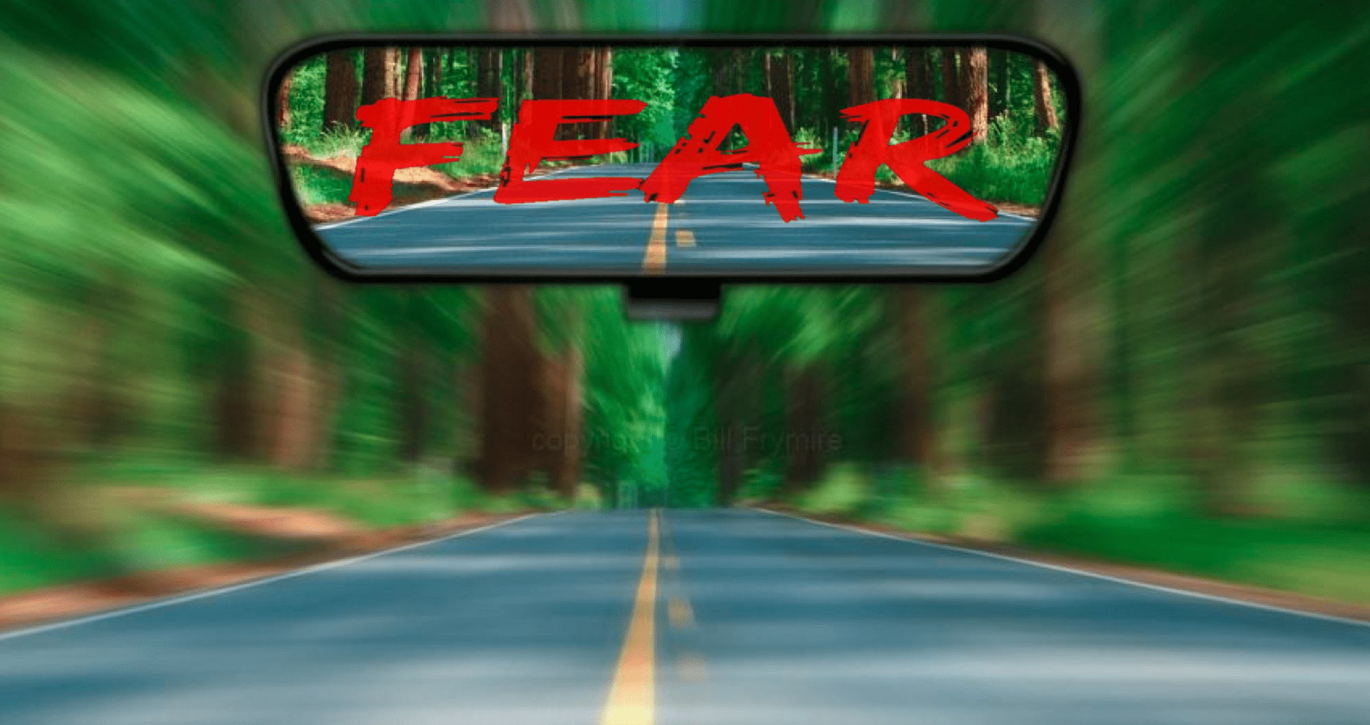 Rear-view mirror in car with word fear in it