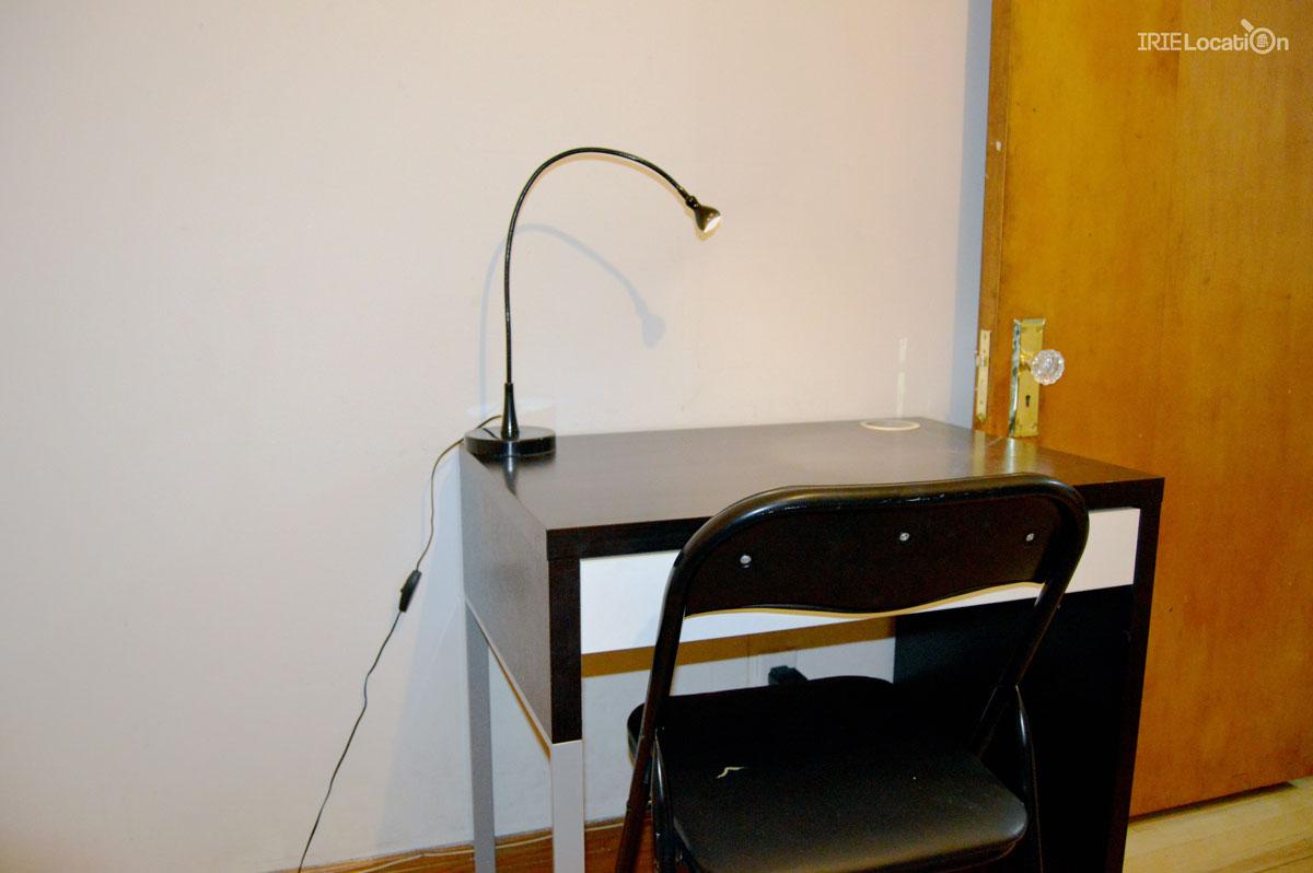 Chambre étudiante incluant bureau, lampe et chaise