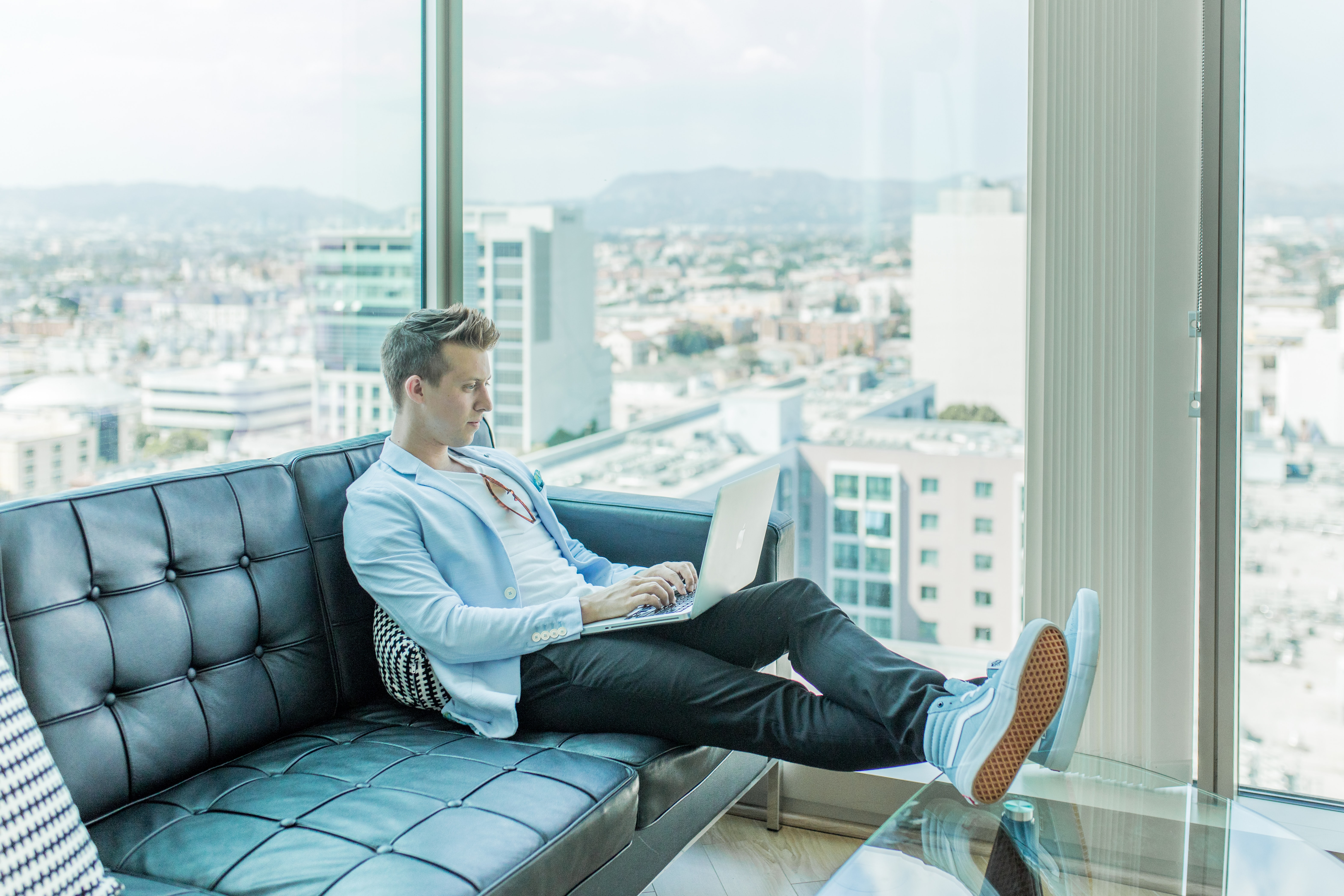 A young man sitting on a black leather couch, feet up, with his MacBook on his lap; working. Behind him, we can see the city through the windows