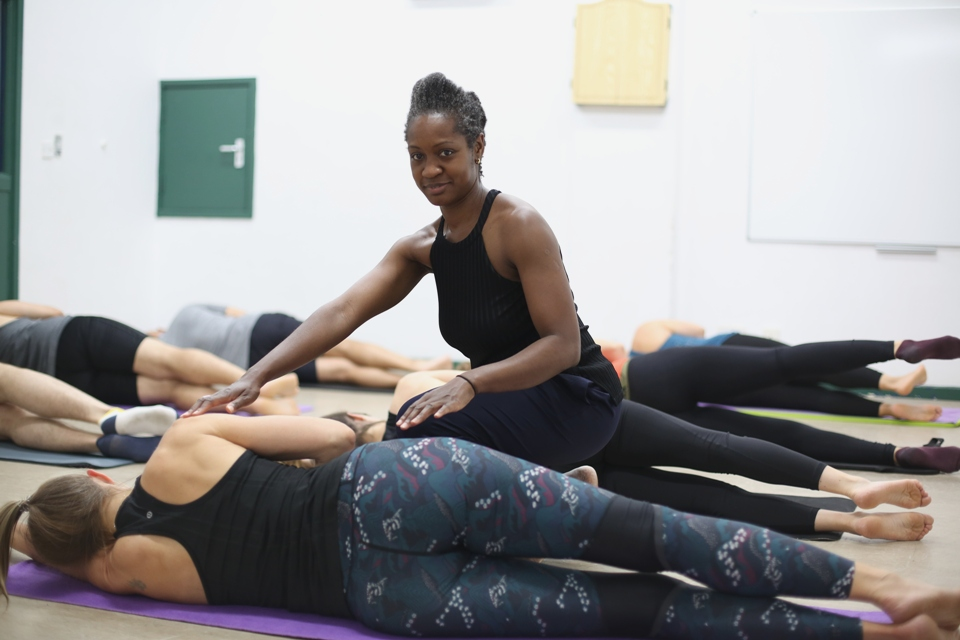 Woman teaching Pilates with woman lying on mat.