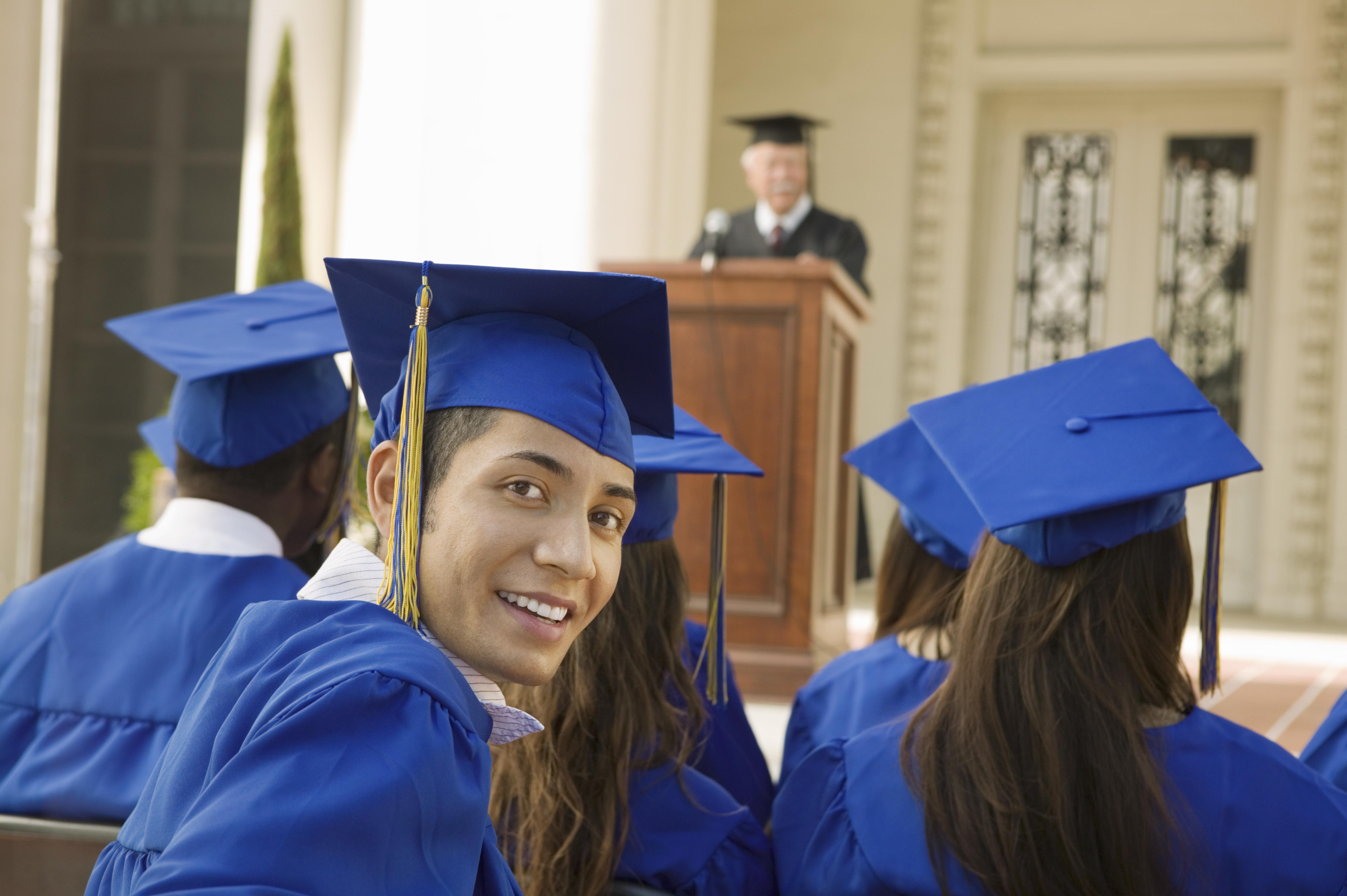 Hispanic student in graduation gown and graduation cap
