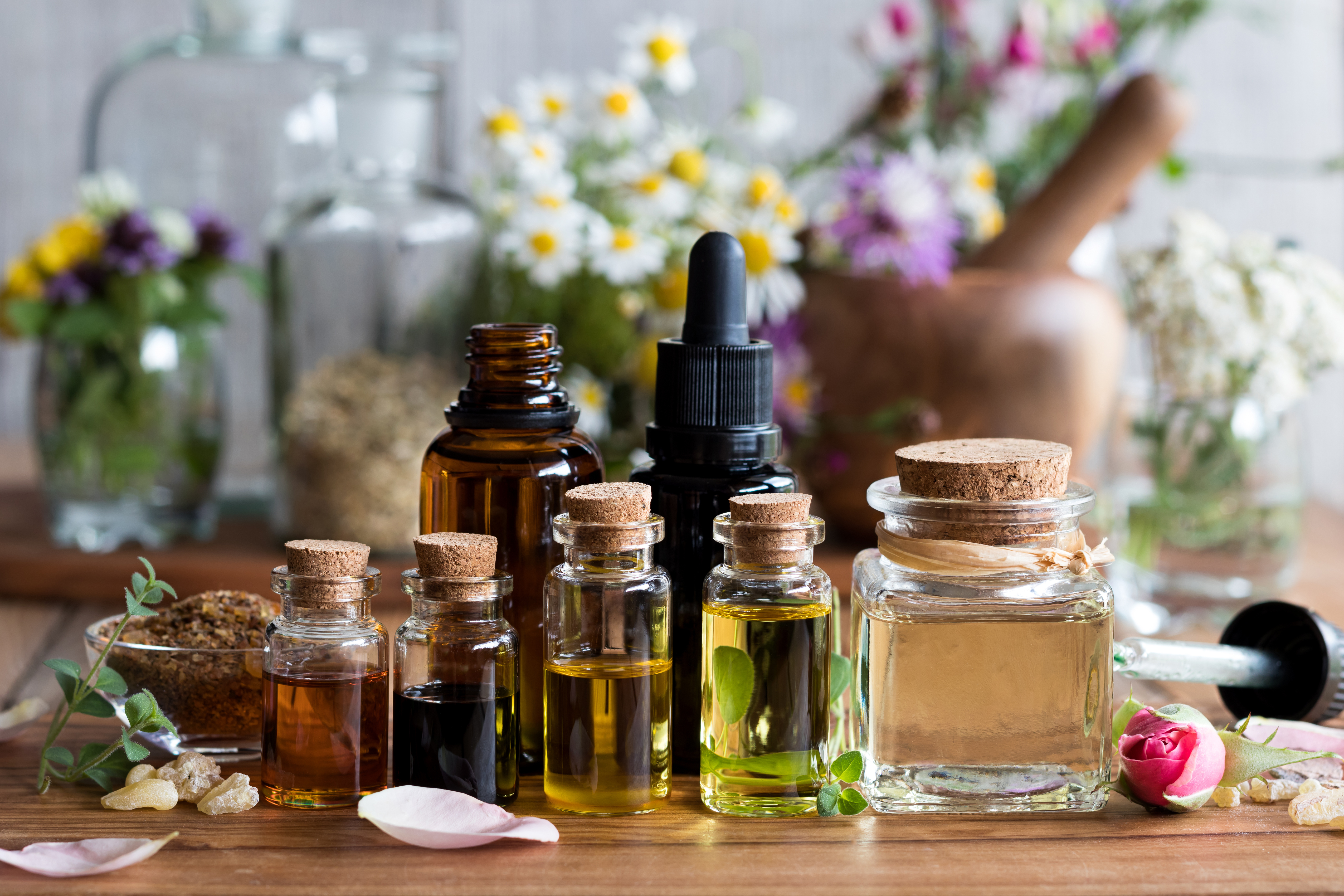 bottles of essential oils with daisies in background