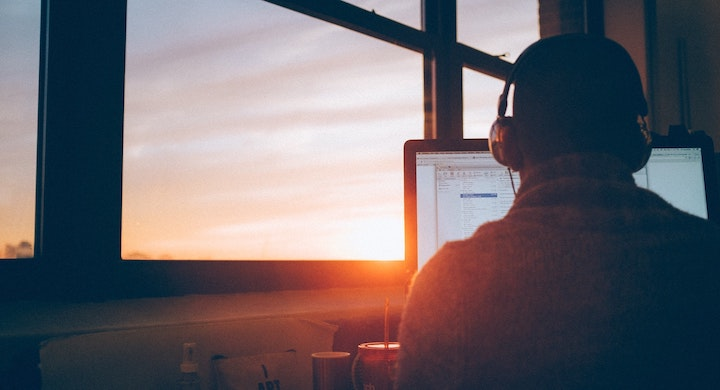 Man sitting at a computer with headphones on; next to him, sunset visible through the window