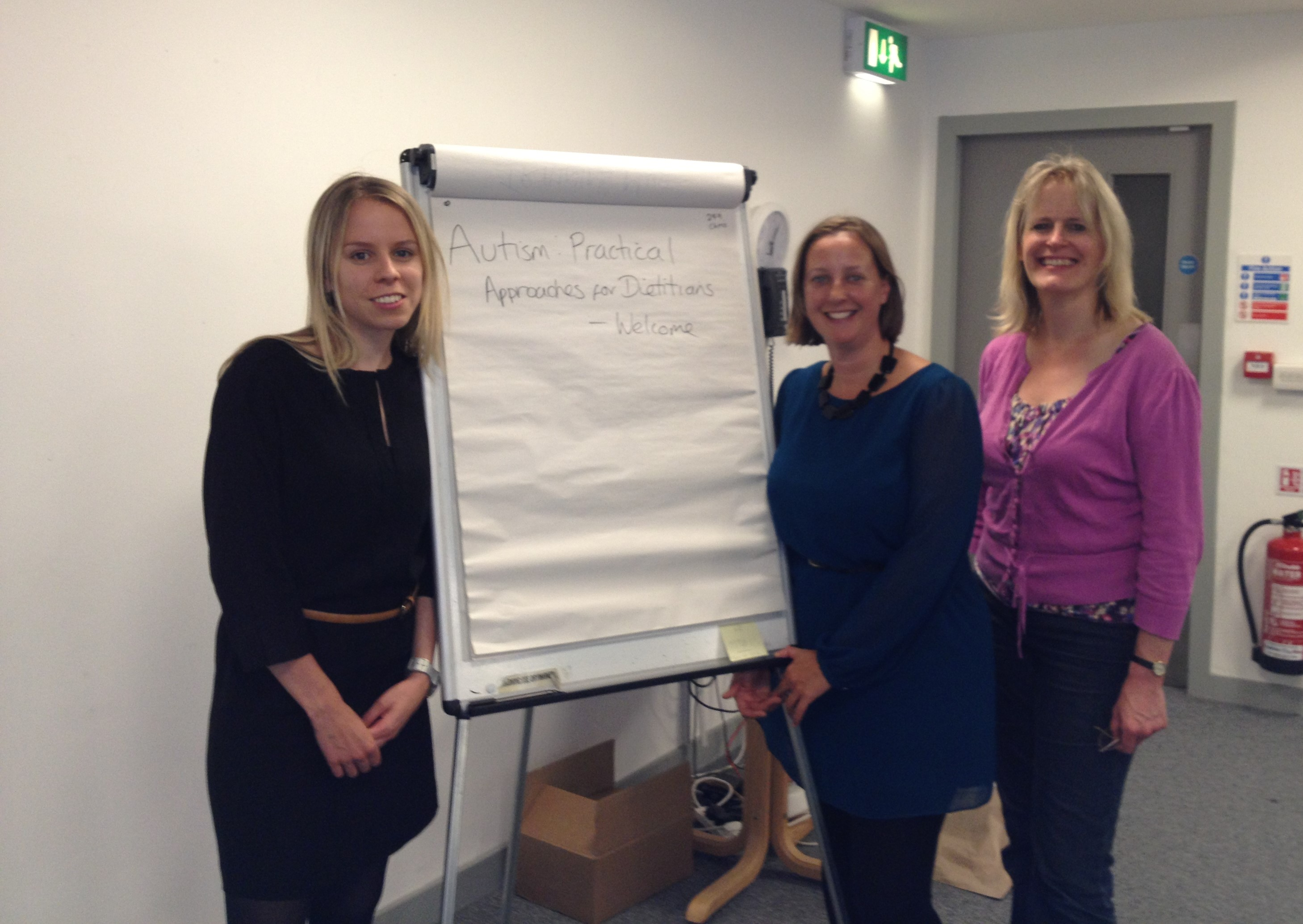 A picture of three white women stood in front of a flipchart