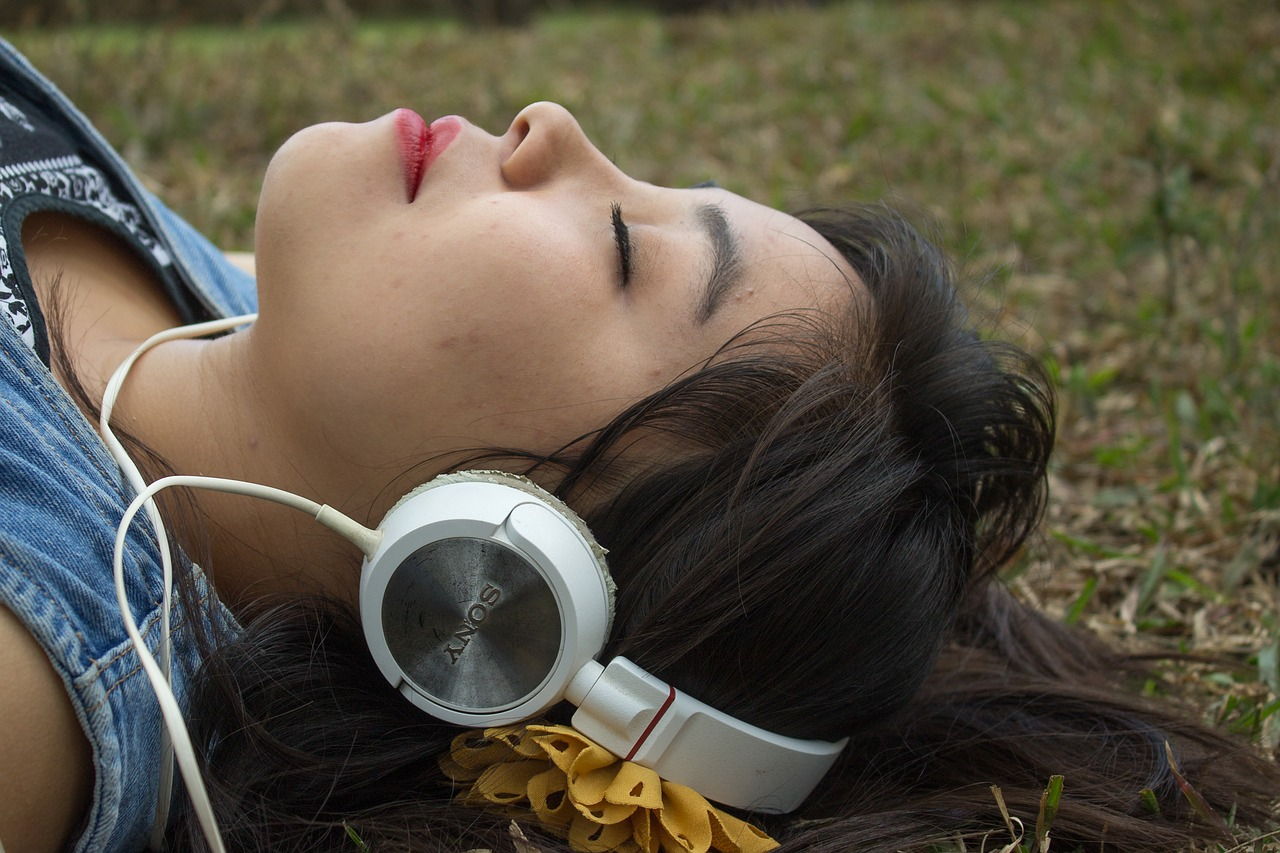 Woman listening to guided meditation on headphones.