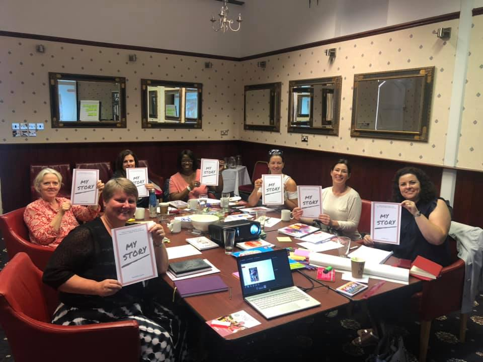 Writing workshop, room of ladies holding their finished workbooks