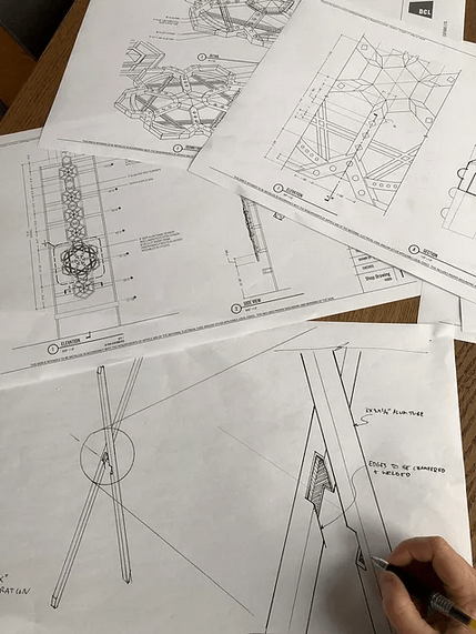 hand with pen and papers with technical drawings