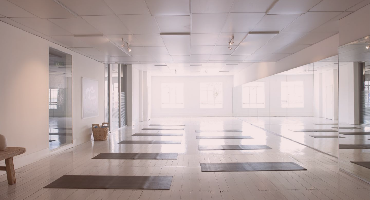 Brightly lit fitness studio with mats on the floor