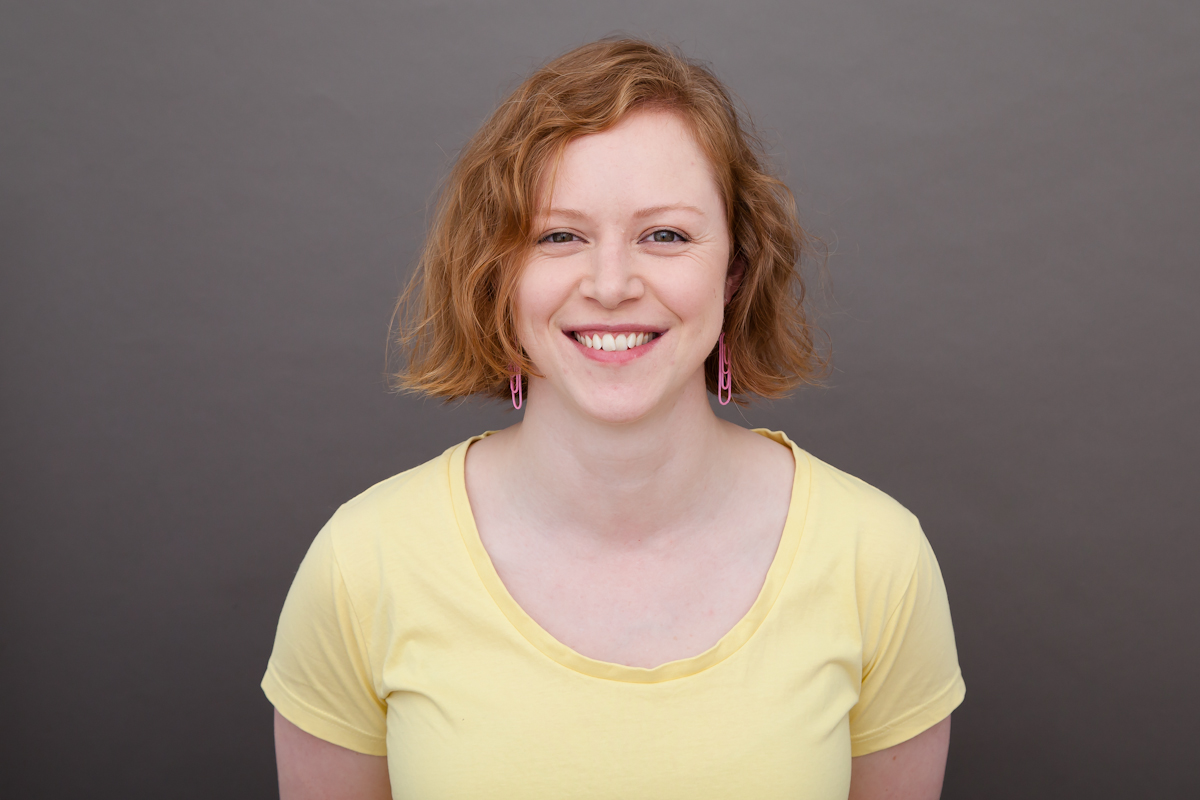 Katie Goudie is wearing a yellow tshirt and pink paperclip earrings. She is standing in front of a grey backdrop and is smiling widely.