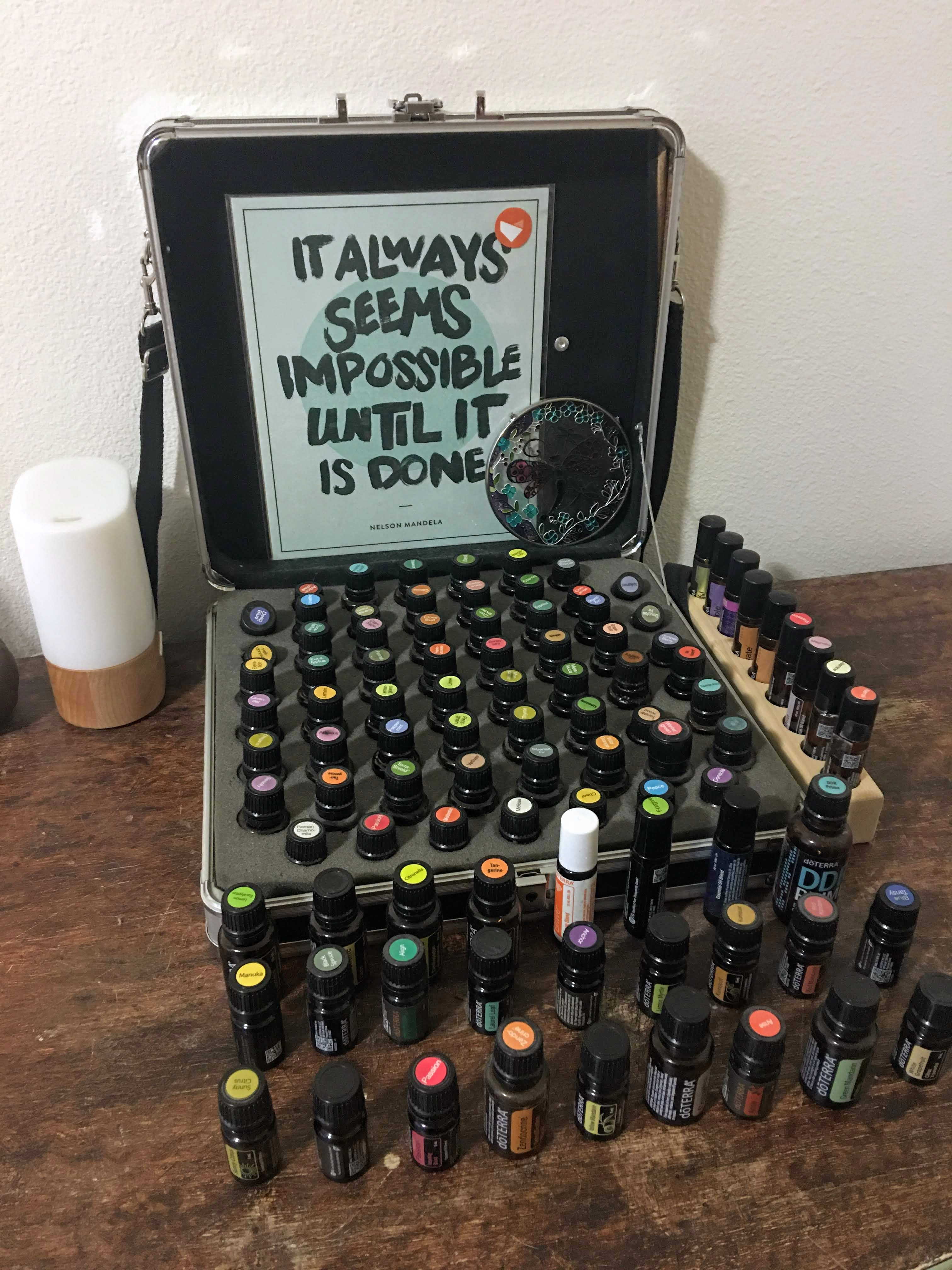(Photo of my oil case and oils set up on top of my dresser, with the diffuser nearby). Sign reads: It always seems impossible until it is done. -Nelson Mandela.
