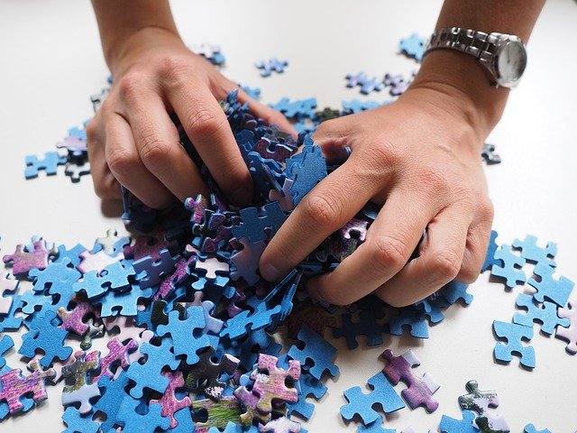 hands full of puzzle pieces
