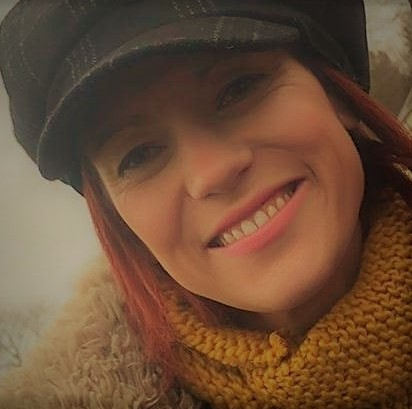 picture of a woman smiling and wearing a hat & coat