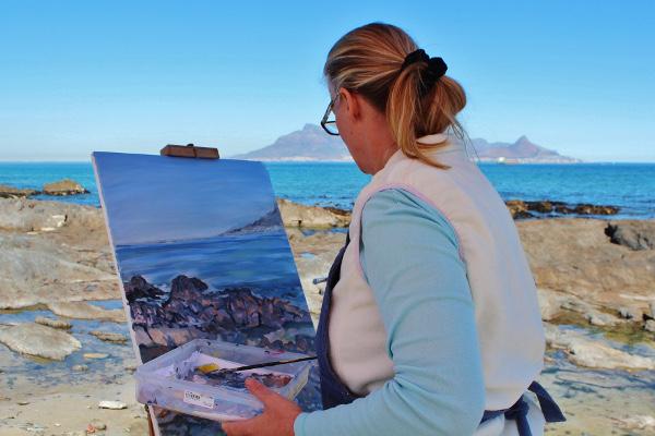 Taiteilija maalaa rannalla