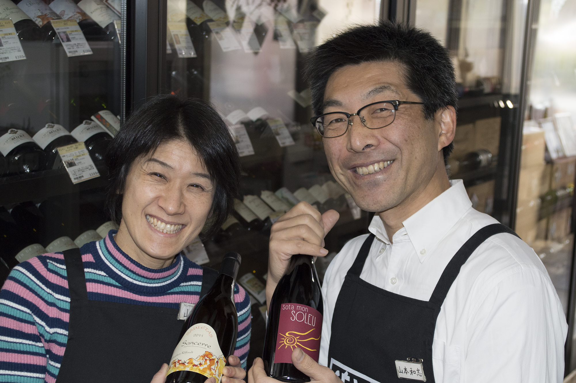 ワインセラーの前でワインボトルをもち微笑む講師の山本夫婦