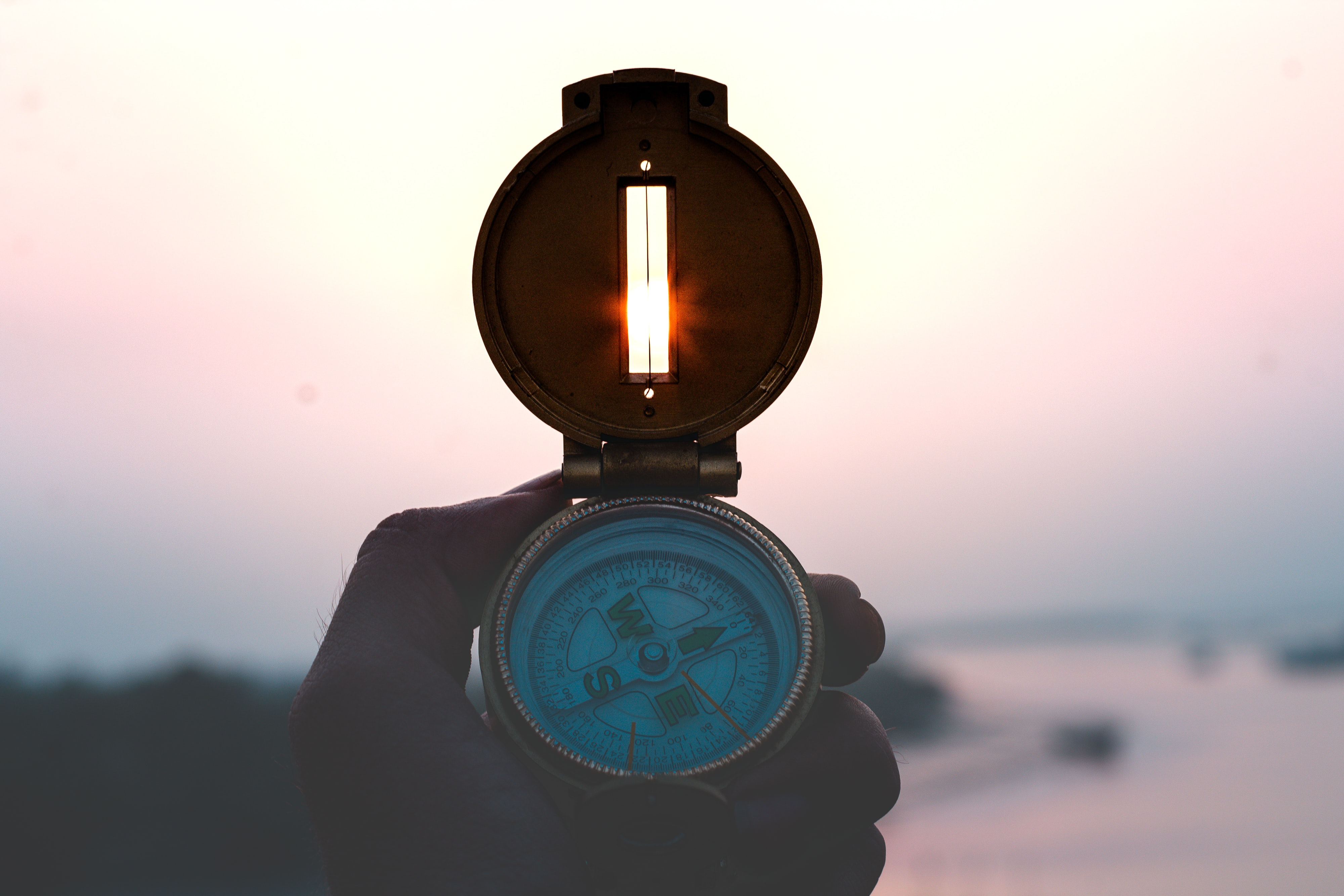 A compass being used at sunset - Goal Success Program
