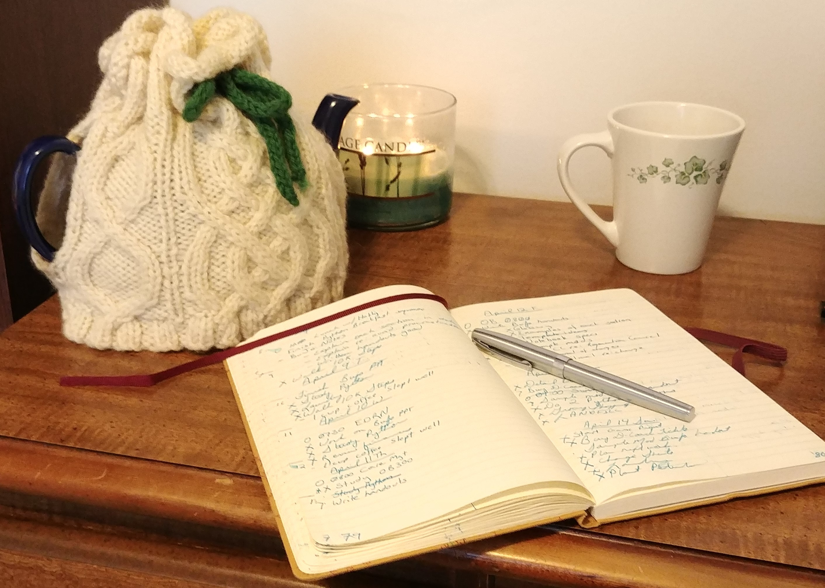 A notebook, candle and teapot with cozy