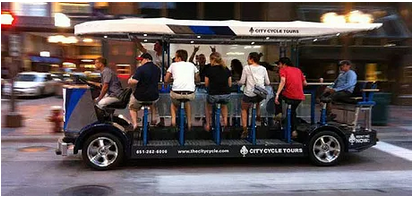 pedal pub with people going down city street