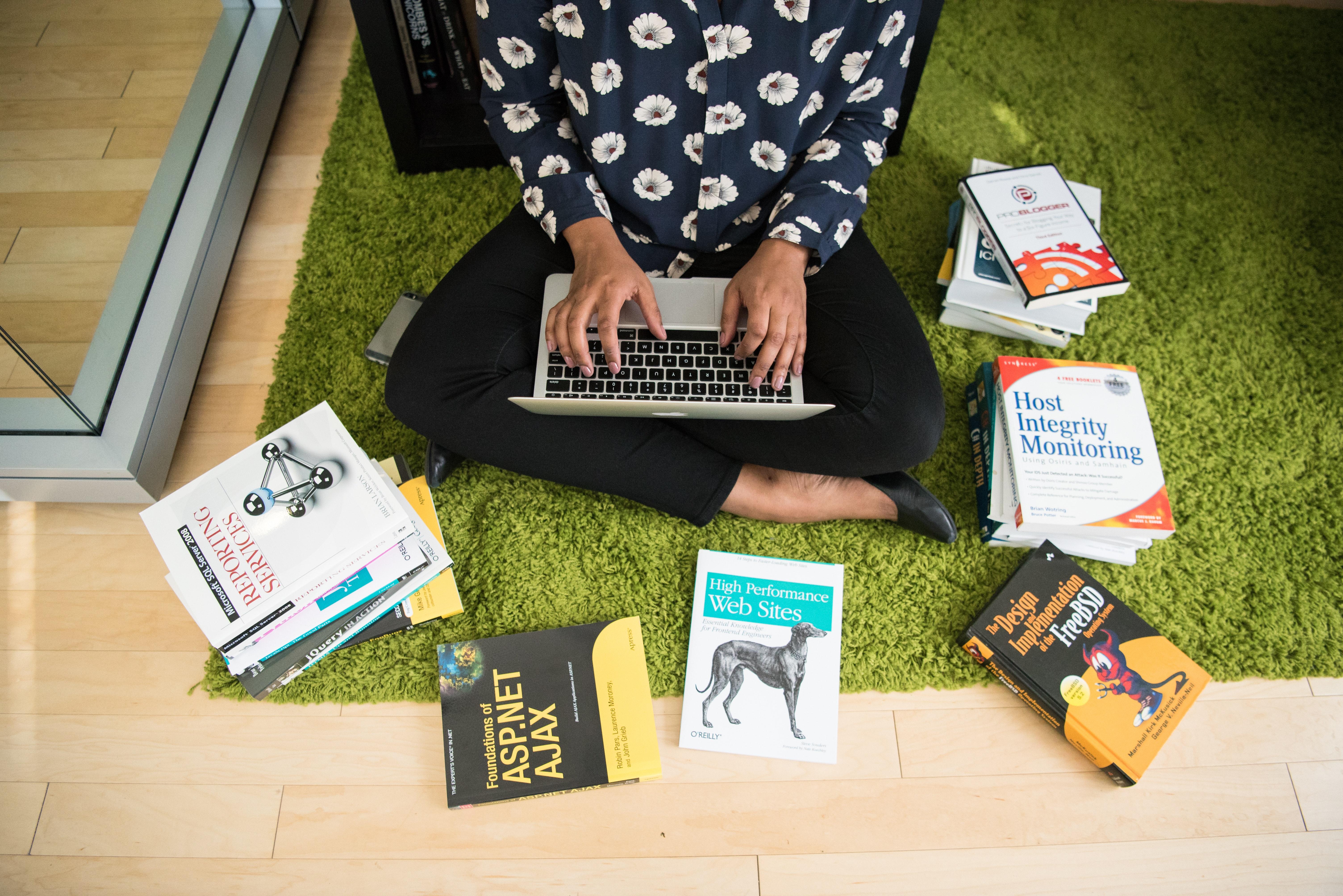 Femme avec un MacBook Air avec des livres en programmation